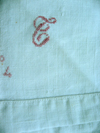 An antique bedsheet with cross stitched monogam and numbering